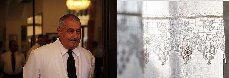 Kellner in einem traditionellen Restaurant in Bologna Zentrum in weißem Frack, rechts: Gardine mit Weintraubenmuster