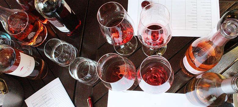 Verkostung von Rosato Weinen aus Italien, aufgezogenen Flaschen auf einen Holztisch in Frankfurt, welcher ist der Beste in der Verkostung? Foto aus der Vogelperpektive auf den Tisch mit den Gläsern und Flaschen