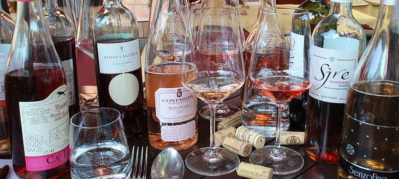 Verkostung von Rosato Weinen aus Italien, aufgezogenen Flaschen auf einen Holztisch in Frankfurt, welcher ist der Beste in der Verkostung?